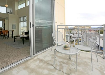 Balcony with a Table and Two Chairs at Paseo Place Apartments