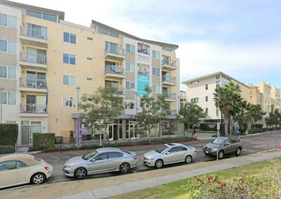 Exterior View of Paseo Place Apartments in San Diego with Cars in the Foreground